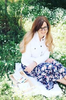 Молодая блондинка в парке лежит в ромашках
