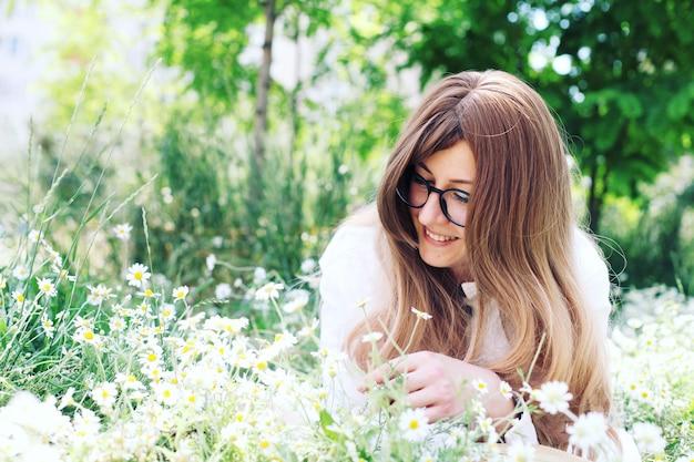 公園の若いブロンドの女性はカモミールにあります