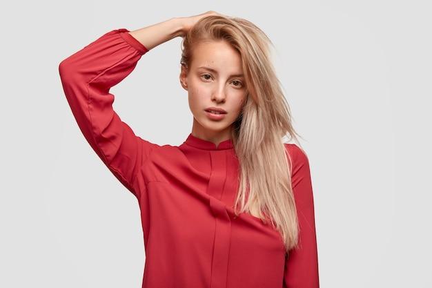 赤いシャツを着た若いブロンドの女性