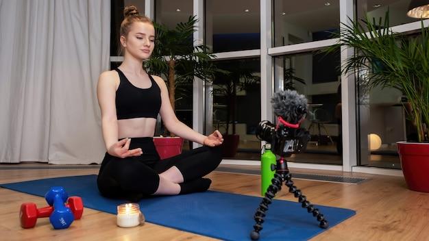 スポーツウェアの若いブロンドの女性は、録音を検討しているヨガマットで瞑想しています