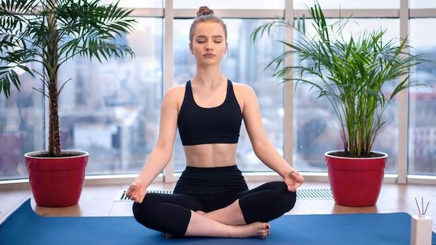 スポーツウェアの若いブロンドの女性は目を閉じてヨガマットで瞑想しています