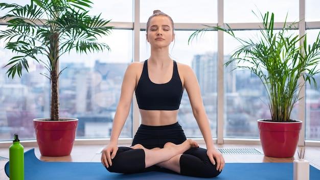 スポーツウェアの若いブロンドの女性は目を閉じてヨガマットで瞑想しています Premium写真