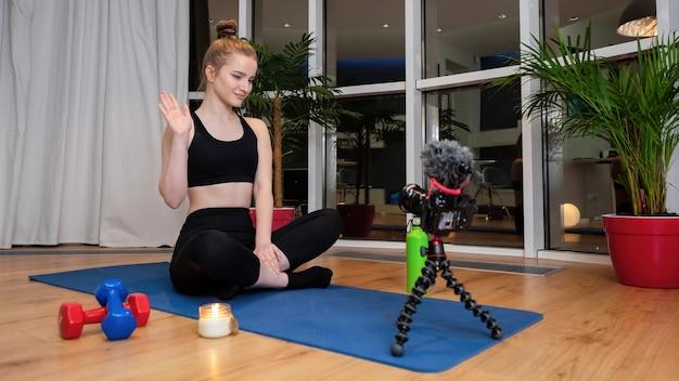 彼女の前の録画ビデオカメラで手を振っているヨガマットの上のスポーツウェアの若いブロンドの女性