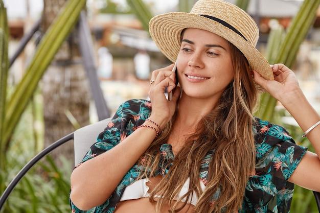 カフェに座っている麦わら帽子の若いブロンドの女性