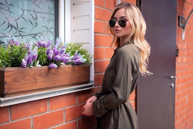 スタイリッシュなメガネをかけた若いブロンドの女性が家の窓の近くに立っています