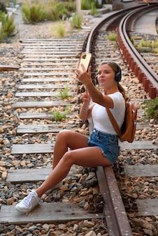 電車のレールに座っている白いtシャツの若いブロンドの女性は彼女の携帯電話で写真を撮る