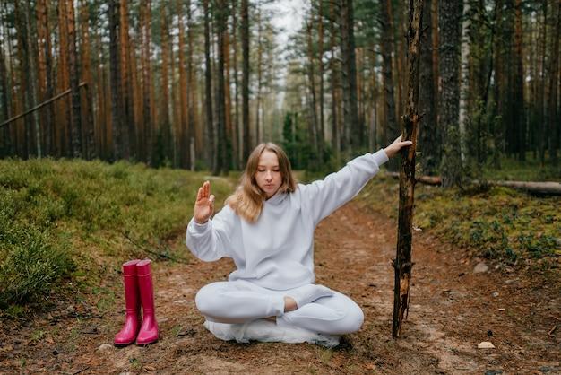 흰색 tracksuit에 젊은 금발의 여자는 숲에 막대기를 들고 묵상