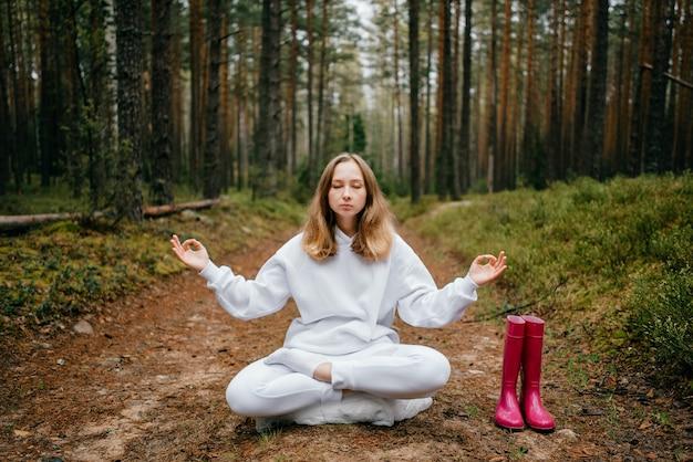 흰색 tracksuit에 젊은 금발의 여자는 숲에서 묵상