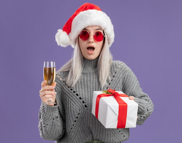 冬のセーターとサンタの帽子の若いブロンドの女性は、紫色の壁の上に立って驚いて驚いたシャンパンのプレゼントとグラスを持っています