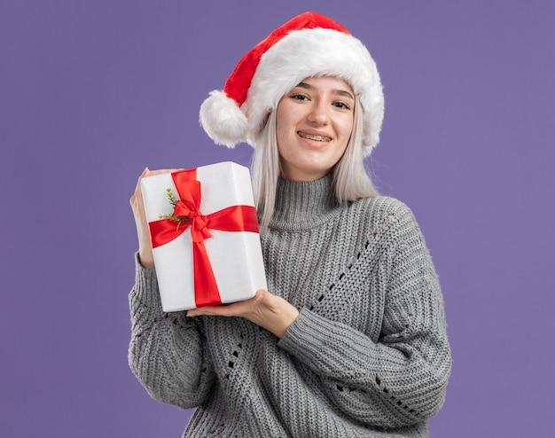 보라색 벽 위에 서 행복 한 얼굴에 미소로 선물을 들고 겨울 스웨터와 산타 모자에 젊은 금발의 여자