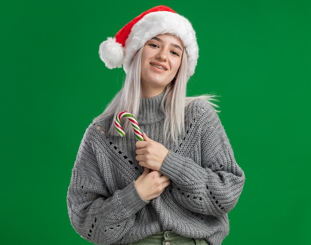 Молодая блондинка в зимнем свитере и шляпе санта-клауса держит конфету, глядя в камеру, счастливая и позитивная улыбка, стоя на зеленом фоне