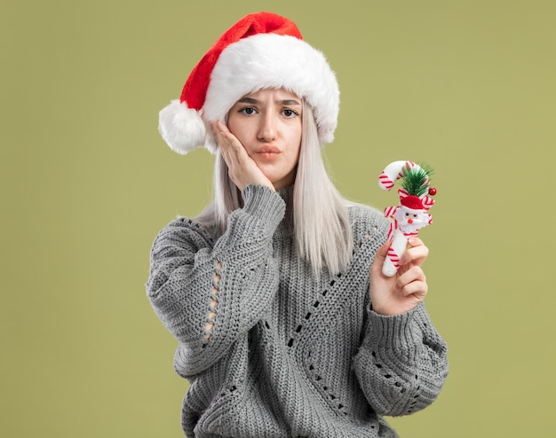 겨울 스웨터와 산타 모자에 젊은 금발의 여자 크리스마스 사탕 지팡이 들고 녹색 벽 위에 서 혼란