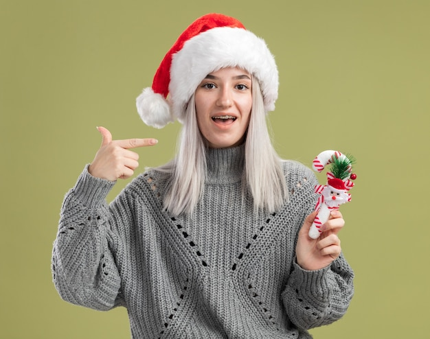 겨울 스웨터와 산타 모자에 젊은 금발의 여자는 녹색 벽 위에 유쾌하게 서 웃고 자신에 검지 손가락으로 가리키는 크리스마스 사탕 지팡이를 들고