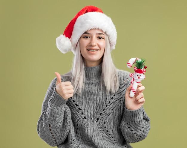 겨울 스웨터와 산타 모자 크리스마스 사탕 지팡이를 들고 젊은 금발의 여자는 유쾌하게 녹색 벽 위에 서 엄지 손가락을 보여주는 미소