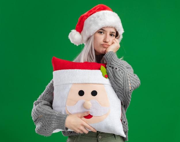 冬のセーターとサンタの帽子の若いブロンドの女性が混乱し、緑の背景の上に立って不満を持ってカメラを見てクリスマス枕を保持しています
