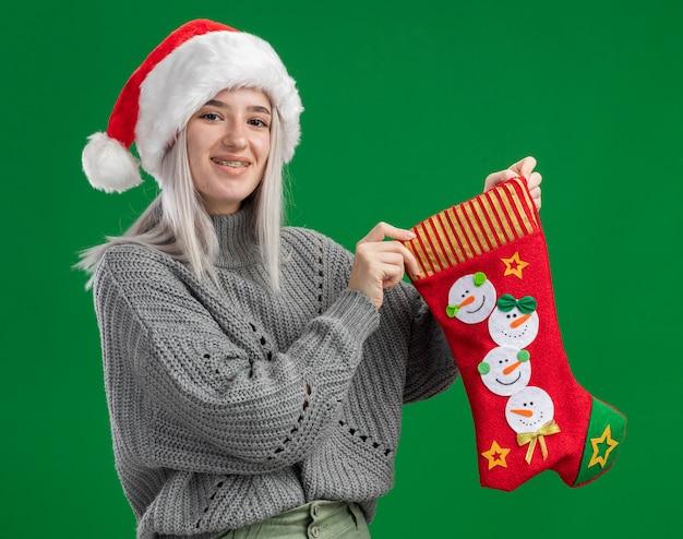 冬のセーターとサンタの帽子の若いブロンドの女性は、緑の背景の上に元気に幸せで前向きに立って笑顔のカメラを見てクリスマスの靴下を保持しています