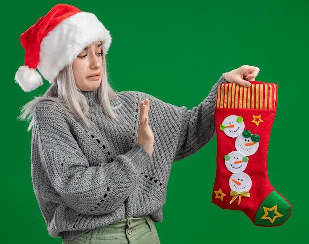 Молодая блондинка в зимнем свитере и шляпе санта-клауса держит рождественский чулок, делая защитный жест рукой, выглядящей смущенной и обеспокоенной, стоя на зеленом фоне