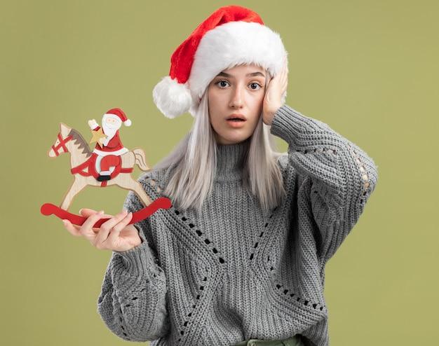 겨울 스웨터와 산타 모자에 젊은 금발의 여자 크리스마스 장난감을 들고 녹색 벽 위에 서있는 그녀의 머리에 손으로 혼동