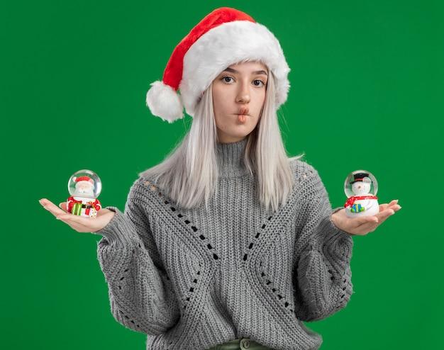 冬のセーターとサンタの帽子の若いブロンドの女性は、緑の背景の上に立っている疑いを持って混乱しているカメラを見てクリスマスのおもちゃのスノードームを保持しています