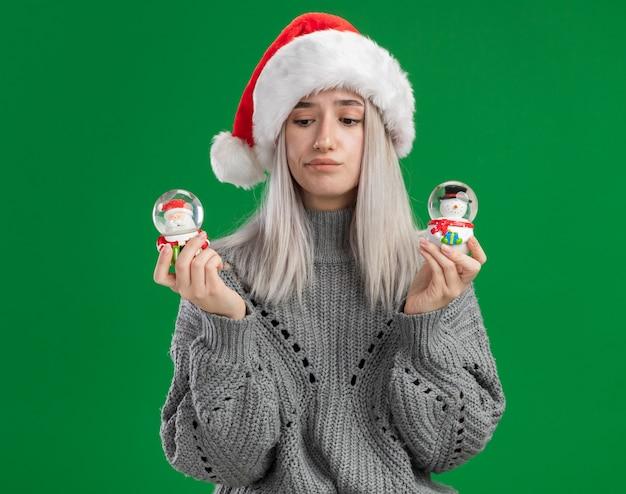 冬のセーターとサンタの帽子の若いブロンドの女性は、緑の背景の上に立って選択をしようとして混乱しているカメラを見てクリスマスのおもちゃのスノードームを保持しています