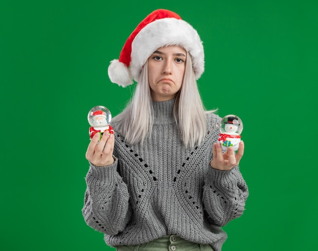 冬のセーターとサンタの帽子の若いブロンドの女性は、緑の背景の上に立っている唇をすぼめる悲しい表情でカメラを見てクリスマスのおもちゃのスノードームを保持しています