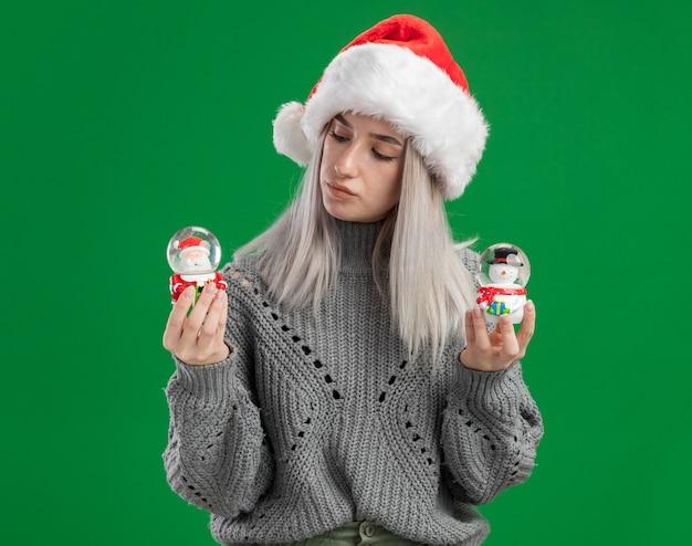 緑の背景の上に立って興味をそそられるように見えるクリスマスのおもちゃのスノードームを保持している冬のセーターとサンタ帽子の若いブロンドの女性