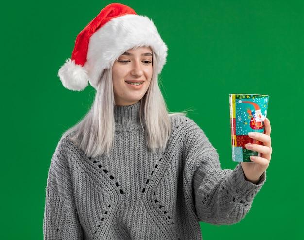 緑の背景の上に立っている顔に笑顔でそれを見てカラフルな紙コップを保持している冬のセーターとサンタ帽子の若いブロンドの女性