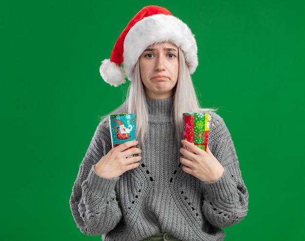 冬のセーターとサンタ帽子の若いブロンドの女性は、緑の背景の上に立っている唇をすぼめる悲しい表情でカメラを見てカラフルな紙コップを保持しています