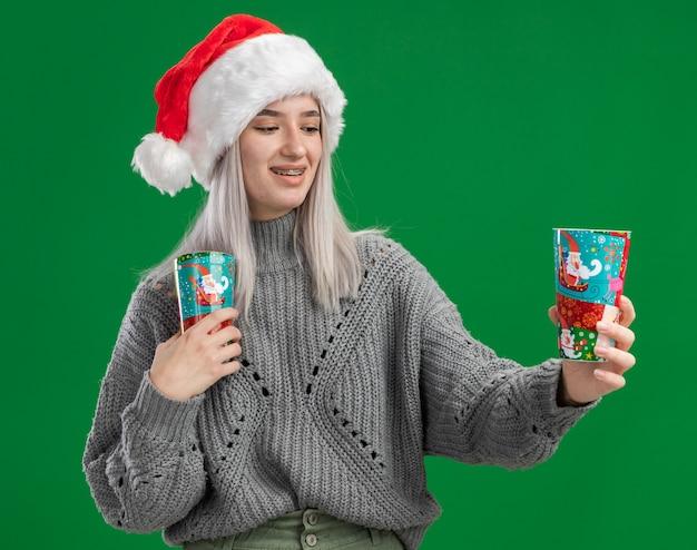 緑の背景の上に立っている幸せな顔で笑顔のカップを見てカラフルな紙コップを保持している冬のセーターとサンタ帽子の若いブロンドの女性