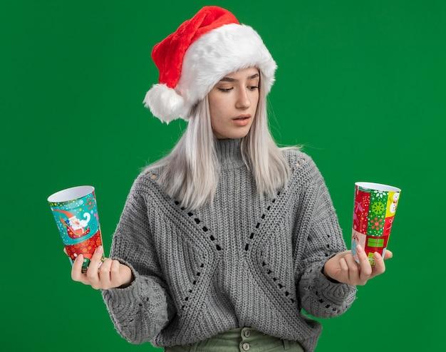冬のセーターとサンタ帽子の若いブロンドの女性は、緑の背景の上に立っている疑いを持って混乱しているように見えるカラフルな紙コップを保持しています