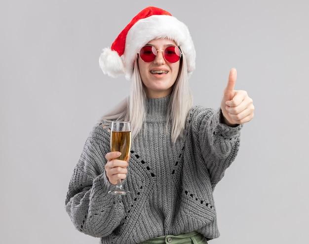 겨울 스웨터와 산타 모자에 젊은 금발의 여자가 샴페인 잔을 들고 행복하고 긍정적 인 미소를 보여주는 엄지 손가락