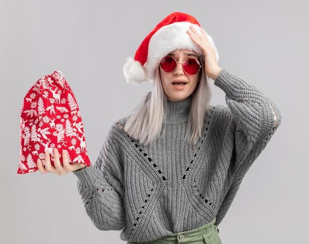 冬のセーターとサンタ帽子の若いブロンドの女性が白い背景の上に立って驚いて驚いたカメラを見てクリスマスプレゼントとサンタの赤いバッグを保持しています