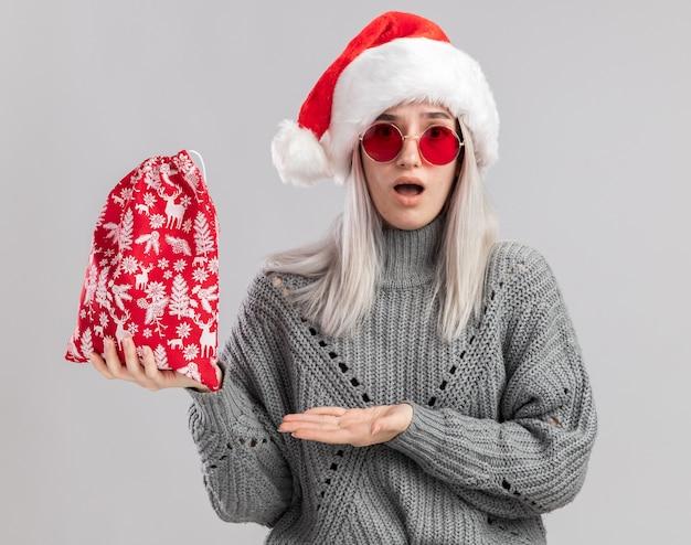 冬のセーターとサンタの帽子の若いブロンドの女性は、白い壁の上に立って驚いて見える手の腕を提示するクリスマスプレゼントとサンタの赤いバッグを保持しています