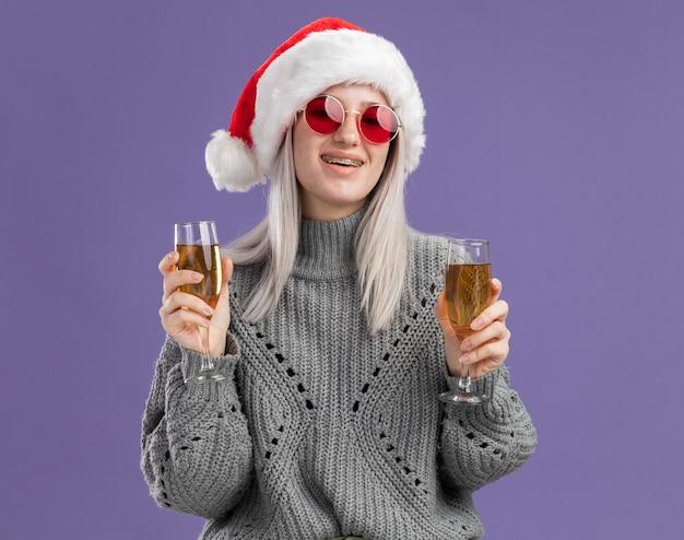 샴페인 두 잔을 들고 겨울 스웨터와 산타 모자에 젊은 금발의 여자는 보라색 벽 위에 유쾌하게 행복하고 긍정적 인 서 웃고