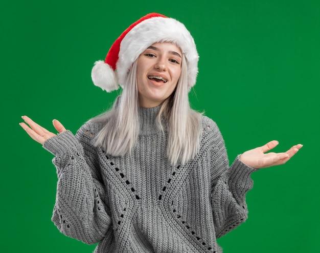 Молодая блондинка в зимнем свитере и новогодней шапке смотрит в камеру, счастливая и позитивная улыбка, бодро стоя на зеленом фоне