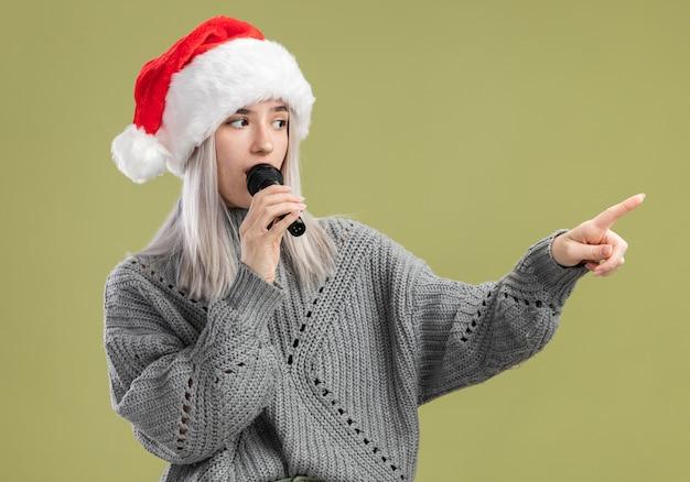 겨울 스웨터와 산타 모자에 젊은 금발의 여자 녹색 벽 위에 서 심각한 표정으로 제쳐두고 뭔가 찾고 검지 손가락으로 마이크를 가리키는 말하기