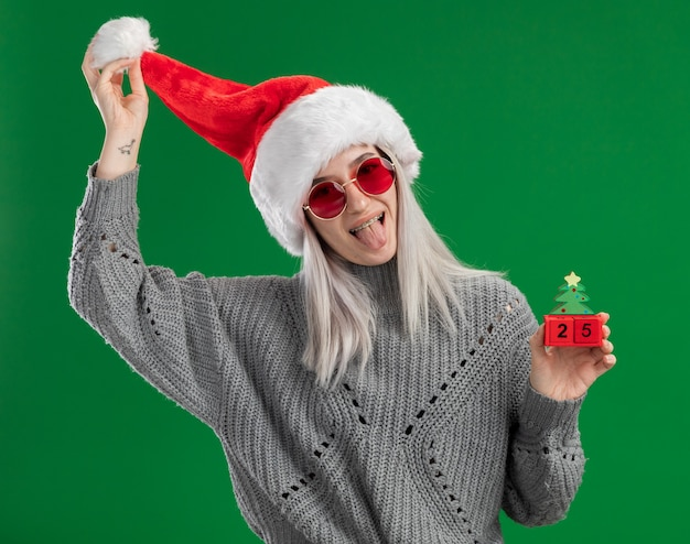 Молодая блондинка в зимнем свитере и шляпе санта-клауса в красных очках держит игрушечные кубики с рождественским свиданием, весело высунув язык, стоя на зеленом фоне
