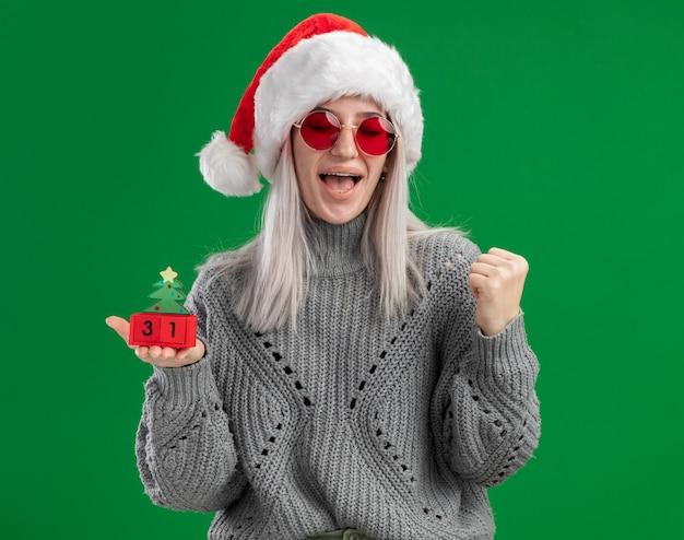 冬のセーターとサンタ帽子の若いブロンドの女性は、緑の背景の上に立って幸せで興奮した拳を握り締めて幸せな新年の日付とおもちゃの立方体を保持している赤い眼鏡をかけています