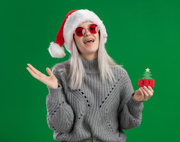 冬のセーターとサンタの帽子の若いブロンドの女性は、幸せな新年の日付と緑の背景の上に元気に立って幸せで前向きな笑顔でおもちゃの立方体を保持している赤い眼鏡をかけています