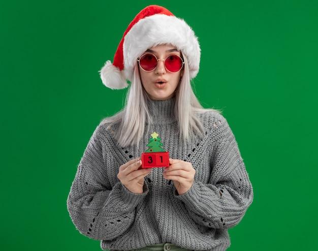 冬のセーターとサンタ帽子の若いブロンドの女性は、緑の背景の上に立って驚いたカメラを見て幸せな新年の日付でおもちゃの立方体を保持している赤い眼鏡をかけています
