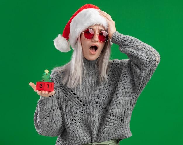 Молодая блондинка в зимнем свитере и шляпе санта-клауса в красных очках держит игрушечные кубики со свиданием с новым годом, выглядит смущенным и обеспокоенным с рукой на голове, стоящей на зеленом фоне