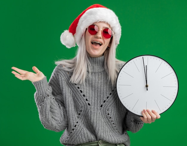 겨울 스웨터와 산타 모자에 젊은 금발의 여자 녹색 배경 위에 카메라 행복하고 흥분 서보고 벽 시계를 들고 빨간 안경을 쓰고