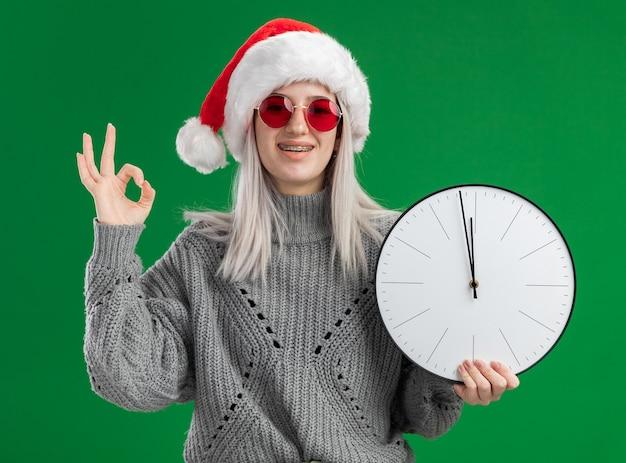 Молодая блондинка в зимнем свитере и шляпе санта-клауса в красных очках держит настенные часы, глядя в камеру, весело улыбаясь, показывая знак ок, стоящий на зеленом фоне