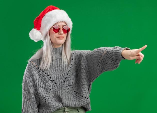 Молодая блондинка в зимнем свитере и шляпе санта-клауса в красных очках смотрит в сторону с серьезным лицом, указывая указательным пальцем на что-то стоящее на зеленом фоне