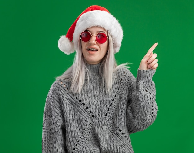 Молодая блондинка в зимнем свитере и шляпе санта-клауса в красных очках выглядит удивленно, показывая указательный палец, имеющий новую идею, стоящий на зеленом фоне