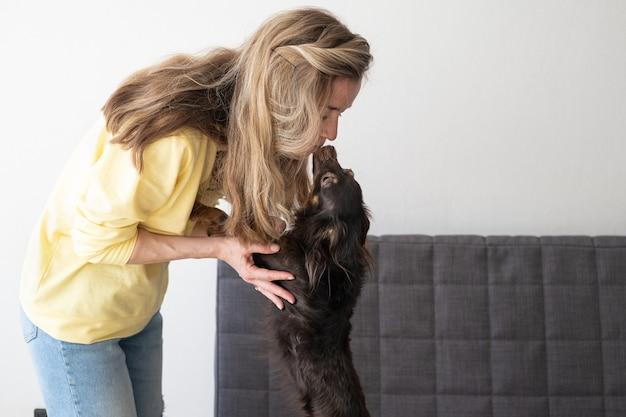 Молодая блондинка в желтом свитере целует смешной коричневый русский той терьер.