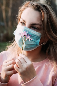 A young blonde woman inhales the smell of a flower through a medical mask