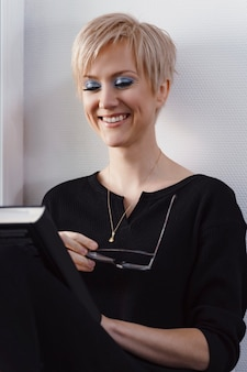 Young blonde woman is reading a book by the window and smiling. glasses in hand