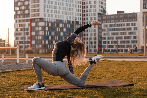 Young blonde woman is stretching on a playground on a yoga mat. apartment buildings and people on background. healthy energetic active lifestyle concept.