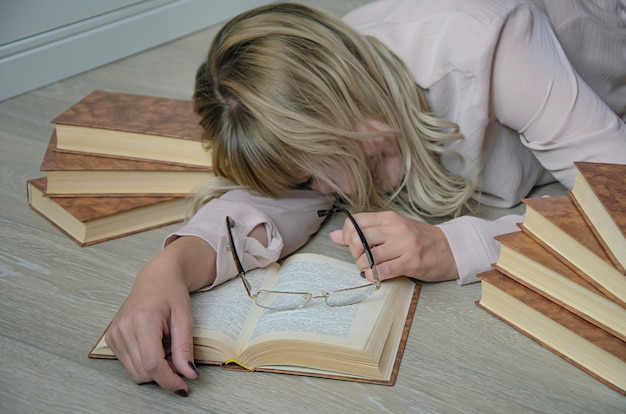 Young blonde woman is surrounded by books had fallen asleep on the floor while studying